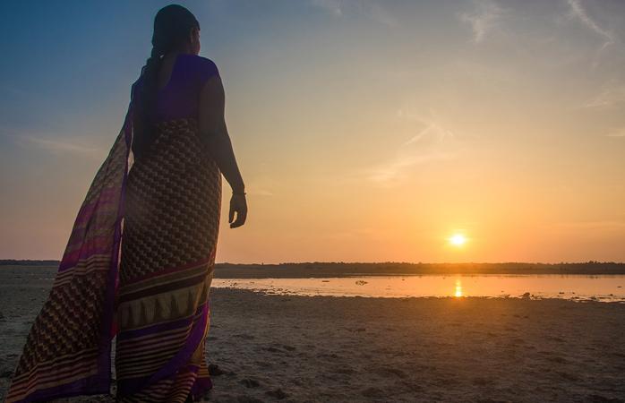 Kobieta w sari obserwująca wschodzące słońce